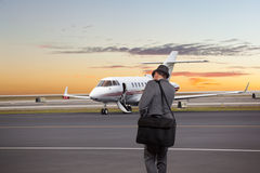 Business man walking toward a private jet. With his laptop case Stock Photo