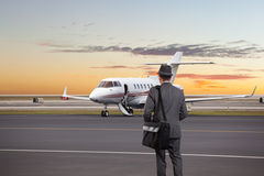 Business man walking toward a private jet Royalty Free Stock Photos