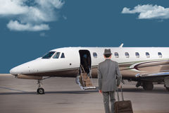 Business man walking toward a private jet Royalty Free Stock Image
