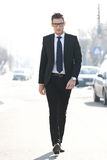 Business man walking towards the camera. Young confident business man walking towards the camera - outdoor picture Royalty Free Stock Image