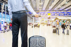 Business man walking travel bag by an international airport Royalty Free Stock Image
