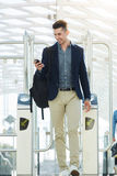 Business man walking through turnstile with mobile phone Stock Photos