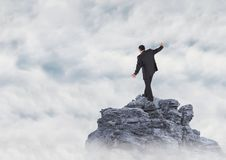 Business man walking up mountain peak in the clouds Stock Photo
