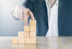Business man walking up next step with fingers on career ladder made from wooden blocks; career or achievement concept royalty free stock photography