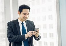 Business man walking and using mobile phone to chatting with fri Royalty Free Stock Image