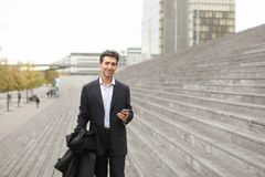 Business man walking using smartphone to watch photos. Business men using smartphone walk, husband watching photos of wife in working trip. Middle-aged American Royalty Free Stock Photography
