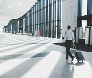 Business man walking with wheeled bag. Business man in formal clothing walking with wheeled bag at airport terminal Royalty Free Stock Photo