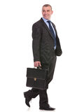 Business man walks with briefcase and looks away Royalty Free Stock Photography