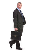 Business man walks with briefcase and looks at you Stock Images