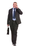 Business man walks with briefcase and on phone Stock Photography