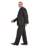 Business man walks and looks at you Stock Photo