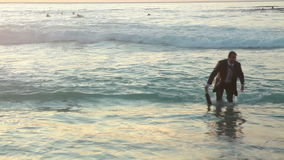 Business man walks out of the ocean stock video footage