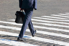 Business man walks on a pedestrian crossing Royalty Free Stock Images