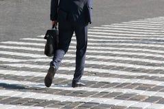 Business man walks on a pedestrian crossing Stock Photography