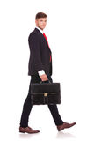 Business man walks to side. Side view of a young business man walking away from the camera with a briefcase and looking at you. isolated on white background Royalty Free Stock Image