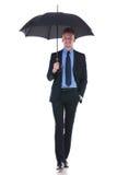 Business man walks with umbrella royalty free stock photo