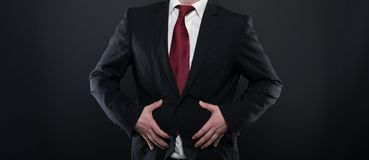 Business man wearing black suit holding belly like hurting. On black background Royalty Free Stock Photography
