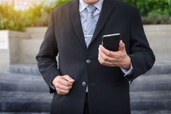 Business man wearing black suit and using modern smartphone in o Royalty Free Stock Photos