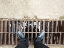 Business man wearing black trousers and black leather shoes looking down to drainage. Royalty Free Stock Image