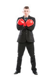 Business man wearing boxing gloves and arms crossed. Standing isolated on white background Royalty Free Stock Images