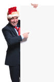 Business man wearing a santa hat is pointing to a blank board. Old business man wearing a santa hat is pointing to a blank board on white background Royalty Free Stock Photos
