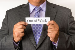 Business man wearing a suit and holding a sign. Neat business person wearing a suit and tie. Holding an out of work sign. Stock Photos