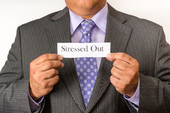 Business man wearing a suit and holding a sign. Neat business person wearing a suit and tie. Holding an stressed out sign. Royalty Free Stock Photos