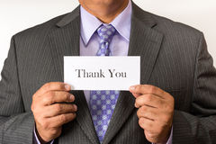Business man wearing a suit and holding a sign. Neat business person wearing a suit and tie. Holding an thank you sign. Business man torso. Person holding a Stock Image