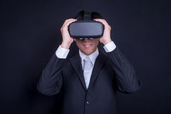 Business man wearing suit playing virtual reality goggles stock photo