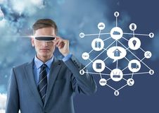 Business man wearing vr glasses standing next to digitally generated connecting icons Royalty Free Stock Image