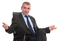 Business man welcomes you from his chair Stock Photo