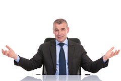 Business man welcomes you from his desk Royalty Free Stock Photos
