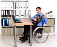 Business man in wheelchair playing the guitar Stock Image