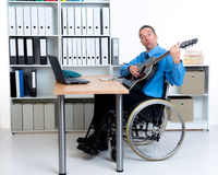 Business man in wheelchair playing the guitar Royalty Free Stock Photography