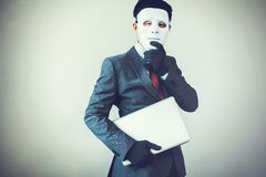 Business man in white mask wearing gloves and stealing computer and digital information - fraud, hacker, theft, cyber crime. Concept stock photo