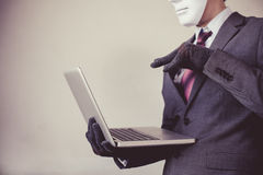 Business man in white mask wearing gloves and using computer - fraud, hacker, theft, cyber crime royalty free stock photo