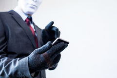 Business man in white mask wearing gloves and using mobile phone. Fraud, hacker, theft, cyber crime concept Stock Photo