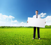 Business man whith empty board in hand on field of grass Royalty Free Stock Images