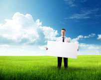 Business man whith empty board in hand on field Royalty Free Stock Image