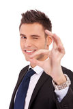 Business man winking with ok sign. Business man winking at you while doing the ok sign on white background Royalty Free Stock Images