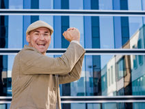 Business man in winning pose. Business man smiling, hands building a victorious  fist Stock Photography