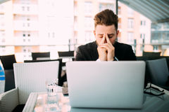 Handsome business man woking at laptop with head ache in cafe shop at terrace. Stock Photography
