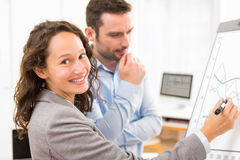 Business man and woman, analysing stats on a paperboard Stock Photo