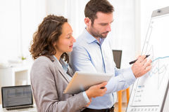 Business man and woman, analysing stats on a paperboard Stock Photography