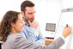Business man and woman, analysing stats on a paperboard Stock Image