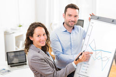 Business man and woman, analysing stats on a paperboard Royalty Free Stock Photo