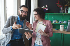 Business man and woman collaborating using tablet and notepad. Young hipster men with women in glasses collaborating in cafe using tablet and notepad Stock Images