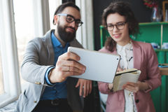 Business man and woman collaborating using tablet and notepad. Young hipster men with women in glasses collaborating in cafe using tablet and notepad Royalty Free Stock Photo