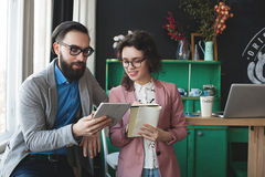 Business man and woman collaborating using tablet and notepad. Young hipster men with women in glasses collaborating in cafe using tablet and notepad Royalty Free Stock Photography
