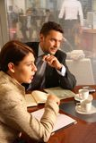 Business man woman conversation. Business man and woman sitting at the desk in the office and having meeting royalty free stock image